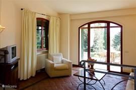 Lichte, ruime salon met openslaande deur en panoramisch uitzicht over de tuinen.  Klik op de foto's voor vergroting