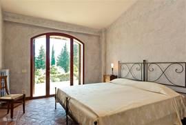 Romantische slaapkamer, terracotta vloer met  smeedijzeren bedden. Heerlijke matras van 200x200 cm en fraai uitzicht.