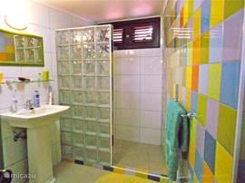 Via een binnendeur komt u van de master bedroom in een eigen kleurrijke badkamer met ruime douche en toilet.