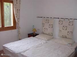 Slaapkamer met inbouwkasten en plafondventilator, rolluiken en muggen netten