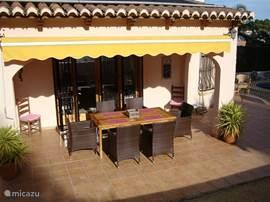 De overdekte naya met zonneluifel. Vanuit de woning direct toegang tot deze tafel en stoelen.