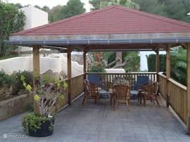 De carpoort is omgetoverd tot een fantastisch plekje om even uit de zon te genieten. Ideale plek voor een bbq, cocktail of kopje koffie met uitzicht over de tuin en het zwembad