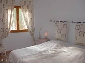 Slaapkamer ensuite met inbouwkasten, plafondventilator, rolluik en muggen netten