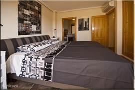 De masterbedroom vanuit eigen terras gezien. Alle slaapkamers beschikken over een eigen airco/verwarming, ruime inbouwkast en moderne kunstwerken aan de muur.