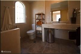 Badkamer behorend bij de master bedroom met: toilet, bidet, wastafel, grote spiegel, bubbelbad/douche en voldoende handdoeken. Er is ook een fohn aanwezig.