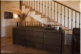 Het dressoir waar u al uw persoonlijke spullen in kunt opbergen. Rechtsom de trap omhoog naar de master bedroom, linksom de stenen trap omlaag naar de overige slaapkamers.