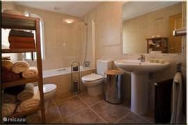 Badkamer met: toilet, bidet, wastafel, spiegel, bad/douche en voldoende handdoeken.