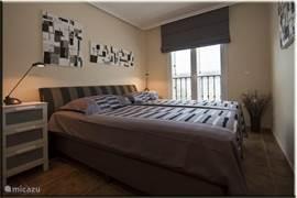 Slaapkamer met een tweepersoons boxspring (1,8x2m).