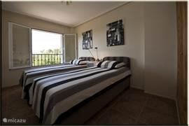 Slaapkamer met twee eenpersoons boxsprings (0,9x2m).