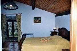 Rustiek ingerichte slaapkamer met uitzicht op de heuvels.
