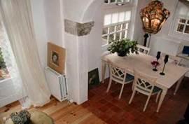 Vanaf de trap gezien ziet u de boog en stukje eet-/ en woonkamer. Aan de zijkant van de woonkamer bevind zich het terras