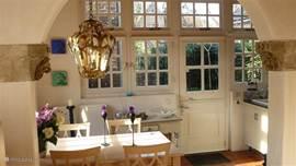 De eetkamer gezien vanuit het woongedeelte. Uitzicht is op de voor/zijtuin