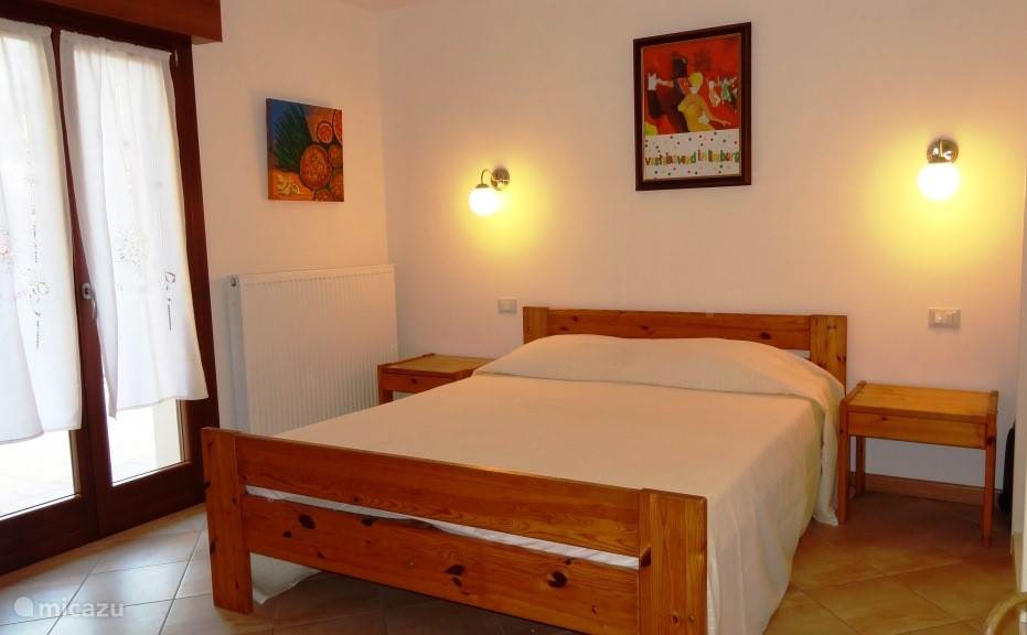 bedroom with double bed, wardrobe, chest of drawers and TV. Double doors to terrace / garden.