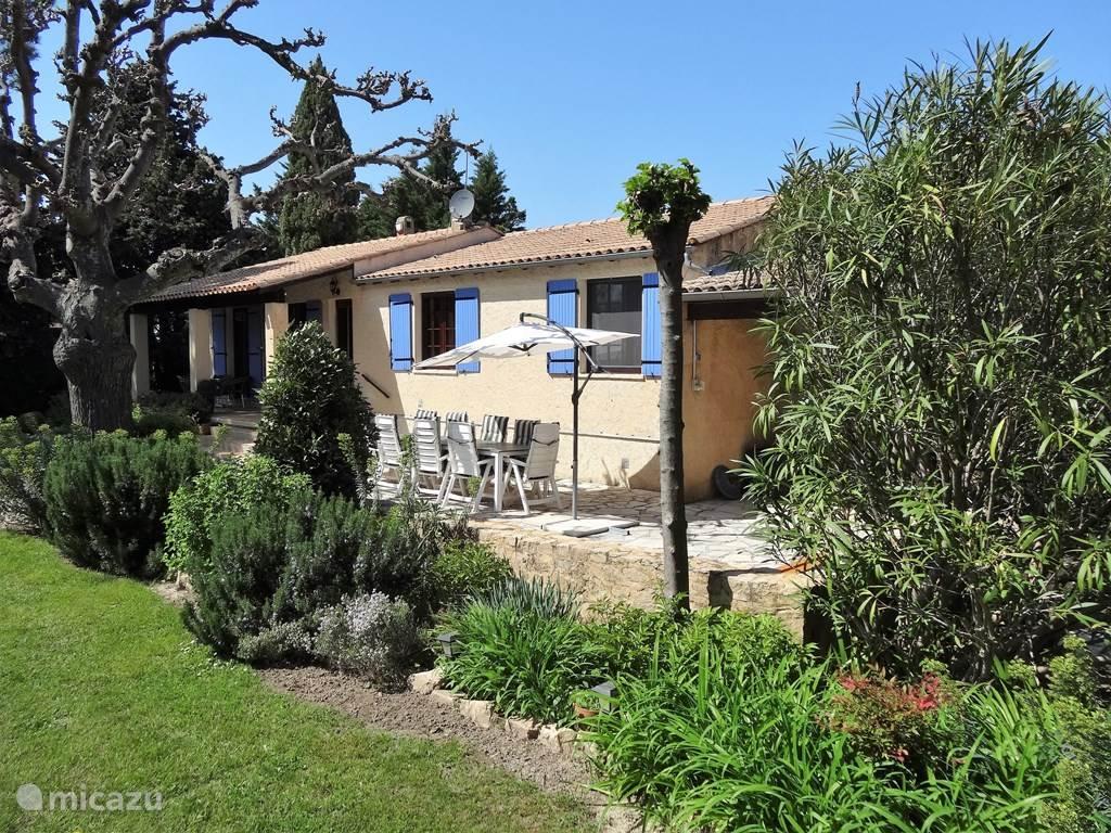 De toegang naar de villa via de overdekte veranda, daarnaast het terras. Net niet op de foto de barbeque met een overdekt gedeelte. De villa is geschikt voor 10 personen. Er zijn 2 woonkamers incl de studio, 5 slaapkamers en 3 badkamers.