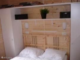 Slaapkamer 1 in het chalet.Een 2-persoonsbed en 2 kasten voor kleding. Boven het bed een handige plank voor spullen en boeken etc.