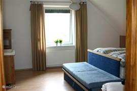 Dit is de grootste slaapkamer met een dubbele box-spring en extra wastafel en een extra bedbank.