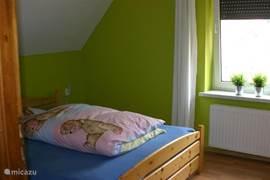 Dit is een kleinere slaapkamer met een 2-persoonsbed een grote kast en een (los) kinderbedje