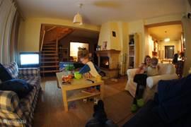 Gezellige woonkamer met haard met op de achtergrond de eetkamer. Rechts daarvan is nog een aparte eetkamer/speelkamer.