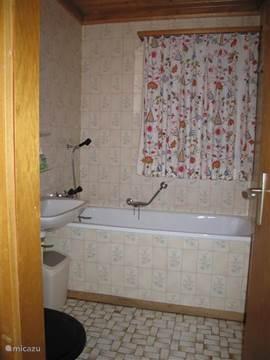 Badkamer met ligbad, wastafel en toilet
