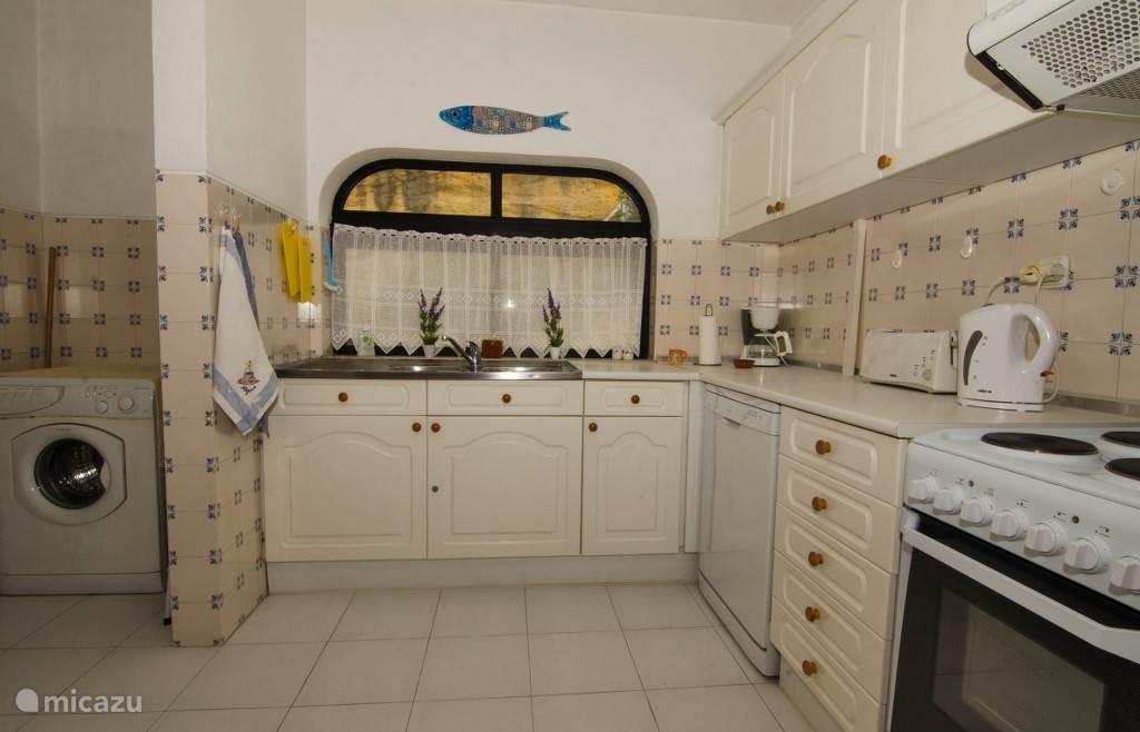 De ruime keuken met vaatwasser, wasmachine, koelkast et cetera