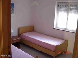 Slaapkamer 2 twee eenpersoons bedden  met hang/ legkast.Ook openslaande ramen met rolluik en vliegen gordijn.