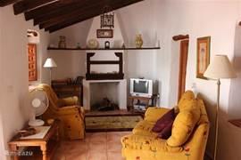 De woonkamer in de woning die ideaal is voor 2 personen. De woonkamer heeft  een open haard. De woning beschikt over een en suite slaapkamer, eigen keuken en binnenplaats en kijkt uit op het centraal, groot terras.