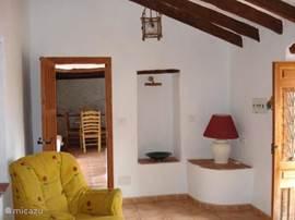 De woonkamer in de lagere woning die leidt naar  een eetgedeelte en toegang tot de keuken.