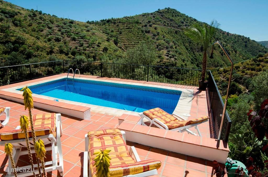 Het zwembad met uitzicht op de vallei. Het zwembad is vrijwel beschut vanaf de weg en heeft dus voldoende privacy.