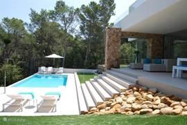 Zicht op zwembad en loungeset