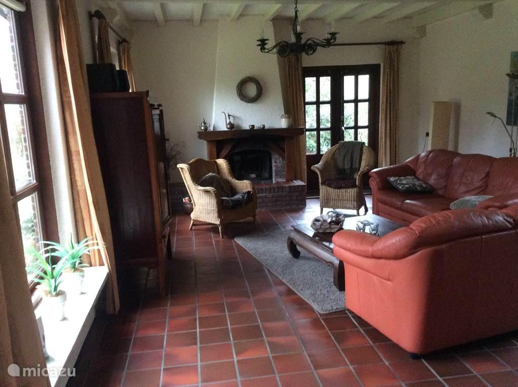 huiskamer met openhaard en openslaande tuindeuren