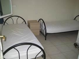 Slaapkamer met twee 1 persoon bedden