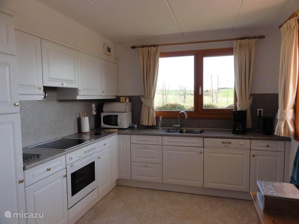 De compleet ingerichte keuken met uitzicht over het dal.