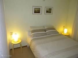 De grote slaapkamer met een twee persoons bed en een kastenwand voor uw kleding en linnengoed.