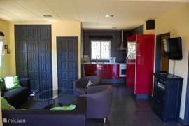 Zitkamer bovenhuis met flatscreen en moderne keuken.