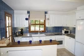 Keuken met Senseo apparaat, waterkoker, keramische kookplaat, oven, vaatwasser en koelvriescombinatie.