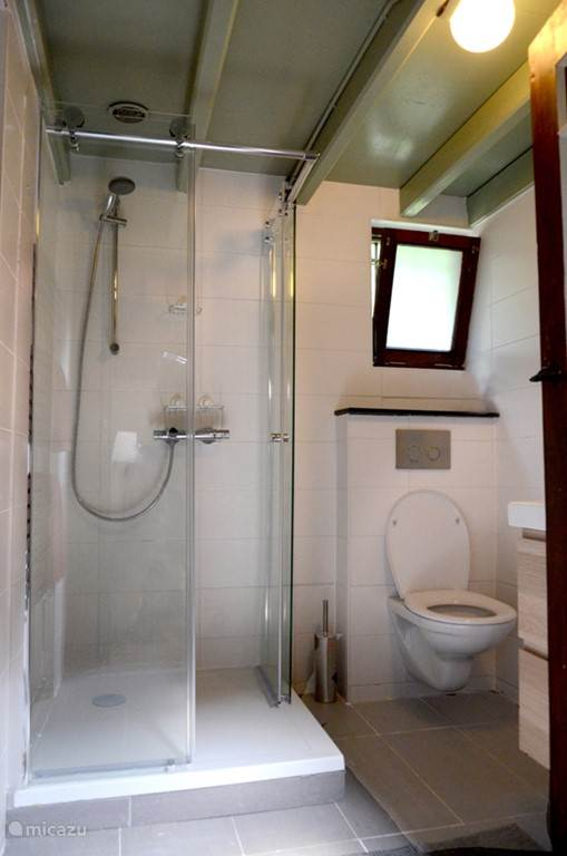 Badkamer met douche, wastafel en WC. Er is geen apart toilet in het huis.