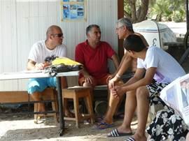 Turkse mannen in gesprek bij het gemeentelijk surfschooltje. Cem Ozertem (eigenaar appartement) met rood shirt in het midden.