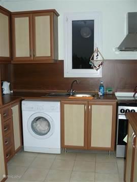 De Keuken met oven, 4 kookplaten, wasmachine, en alle benodigheden om ook zelf in het appartement een maaltijd klaar te maken.