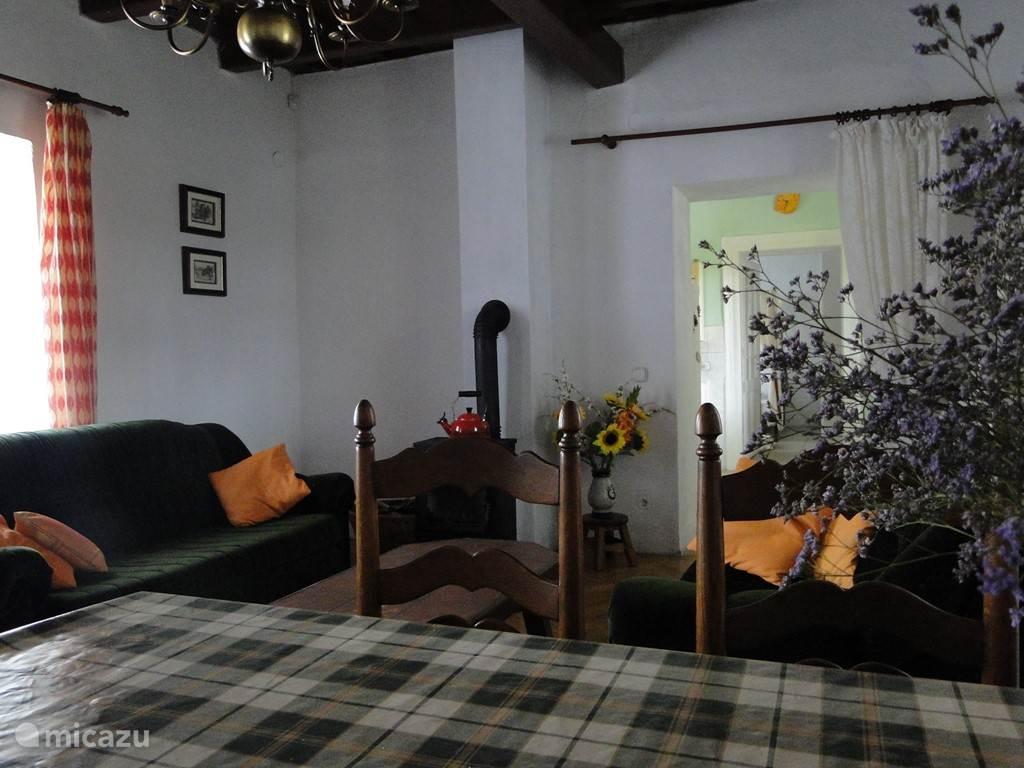 zicht van de living vanaf de eetplaats, je ziet de sofa's en de kachel op de achtergrond.Naast de living zie je de keuken en slaapkamer met de 'masterbedroom'.