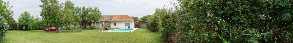 panoramisch zicht op de tuin, op de achtergrond zie je het zwembad en het pomphuis en de studio