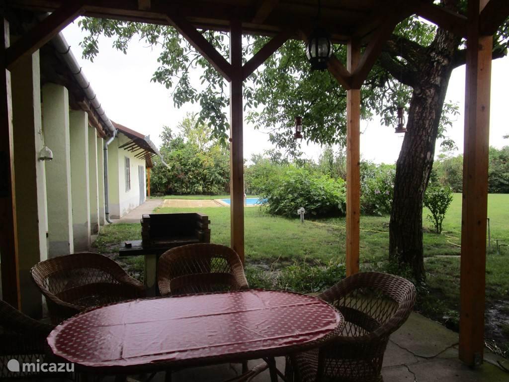 zicht vanop het terras met de bbq. Je ziet het zwembad achter de struiken in de afgesloten tuin. In het huis zijn er 2 vliegedeuren en overal vliegeramen, zo houd je de muggen makkelijk buiten