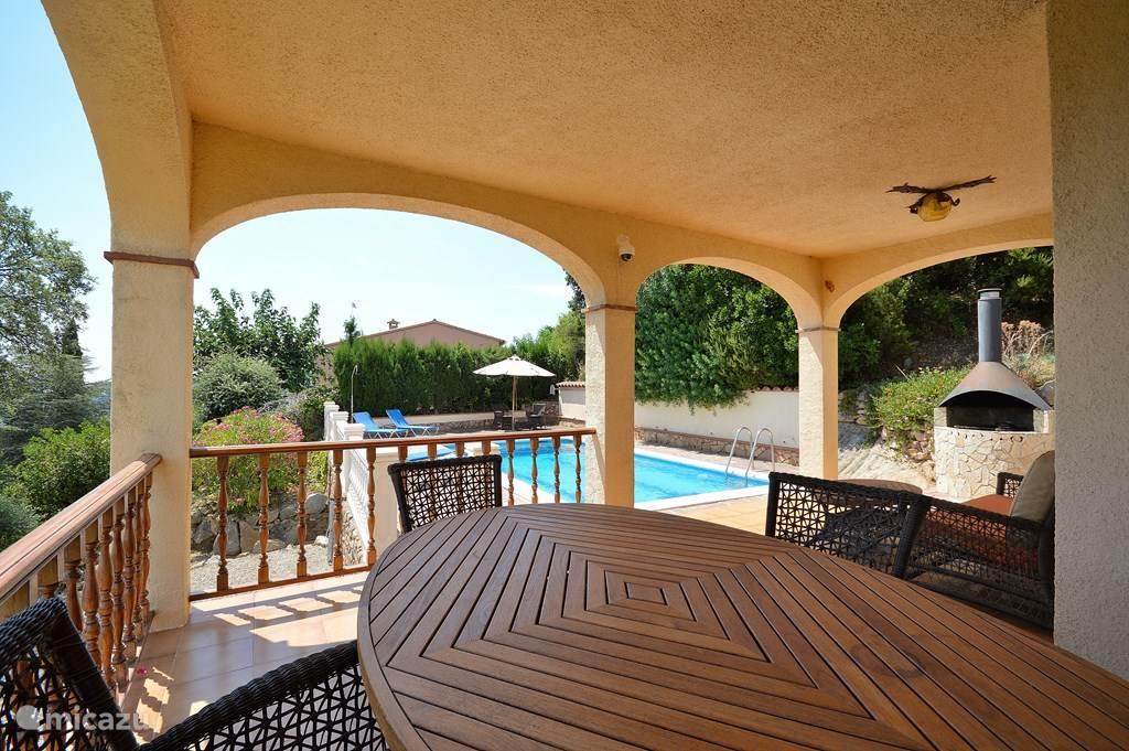 Veranda direkt aan de woonkamer met terras naar zwembad.