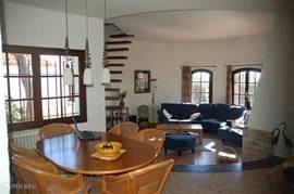 Woon- en eetkamer met de open trap naar de toren (slaap)kamer.