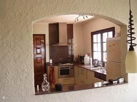 Een complete (half open)keuken waar alle keukenapparatuur direct voor handen is. In de bijkeuken bevindt zich de wasmachine.