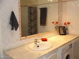 Ensuite badkamer van de grote slaapkamer beneden. Hier staat ook de wasmachine en droger. Er is een toilet, wastafel, bidet en inloopdouche