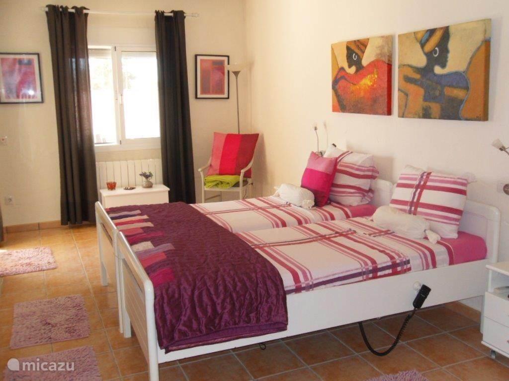 Hele ruime slaapkamer met dubbel bed, schuifpui naar een overdekt terras met zitje. En toegang tot een ruime ensuite badkamer