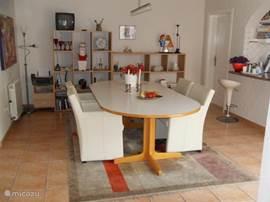 Grote eettafel met stoeltjes en aan de rechterzijde de American Style keuken