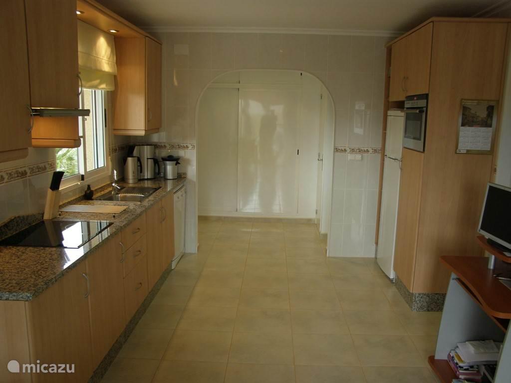 Keuken met keramische kookplaat, afzuigkap, koelkast, vriesvak, combimagnetron, vaatwasser, koffiezetapparaat, waterkoker en citruspers.