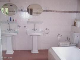 Ruime en comfortabele badkamer met aparte douche en bad.