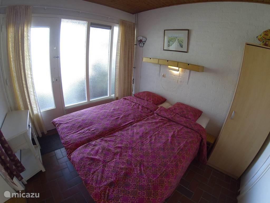 Slaapkamer begane grond met kleine badkamer en toilet.